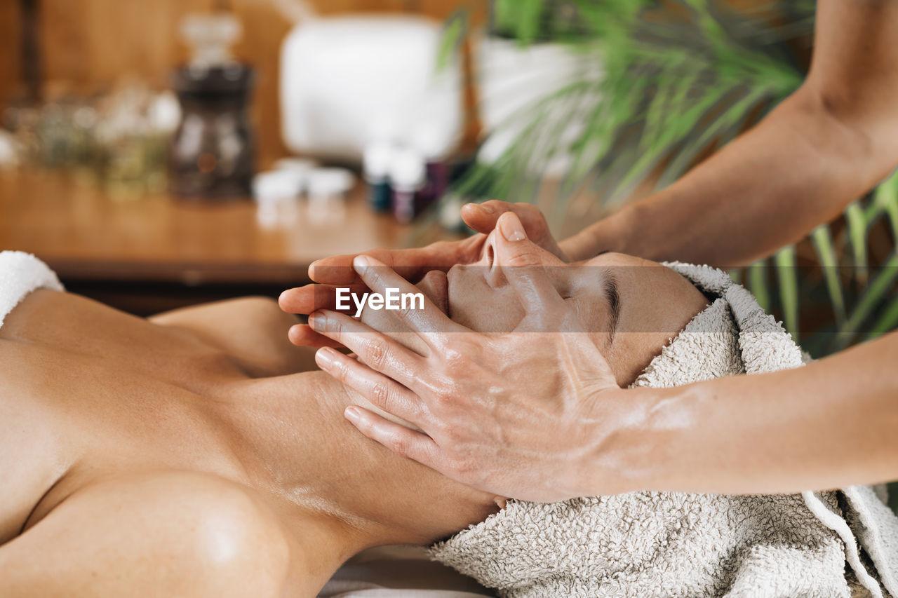 Woman enjoying a professional ayurvedic facial massage with therapeutic oils
