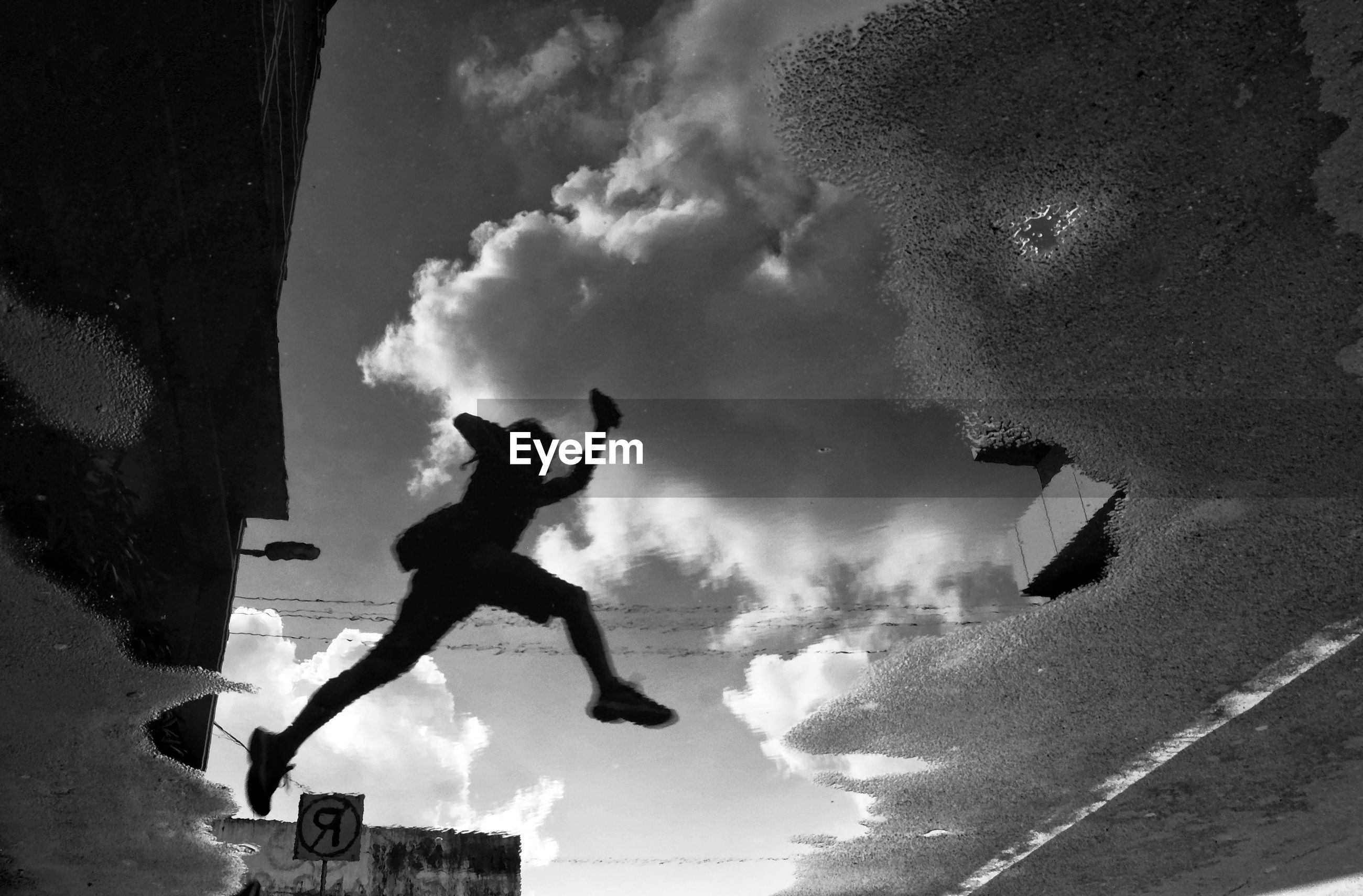 Low angle view of silhouette person jumping in city against sky
