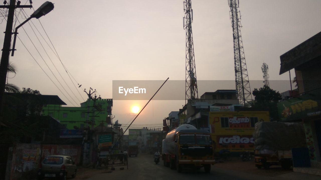 sunset, built structure, sky, transportation, mode of transport, cable, land vehicle, architecture, outdoors, city, no people, electricity pylon, building exterior, technology, day