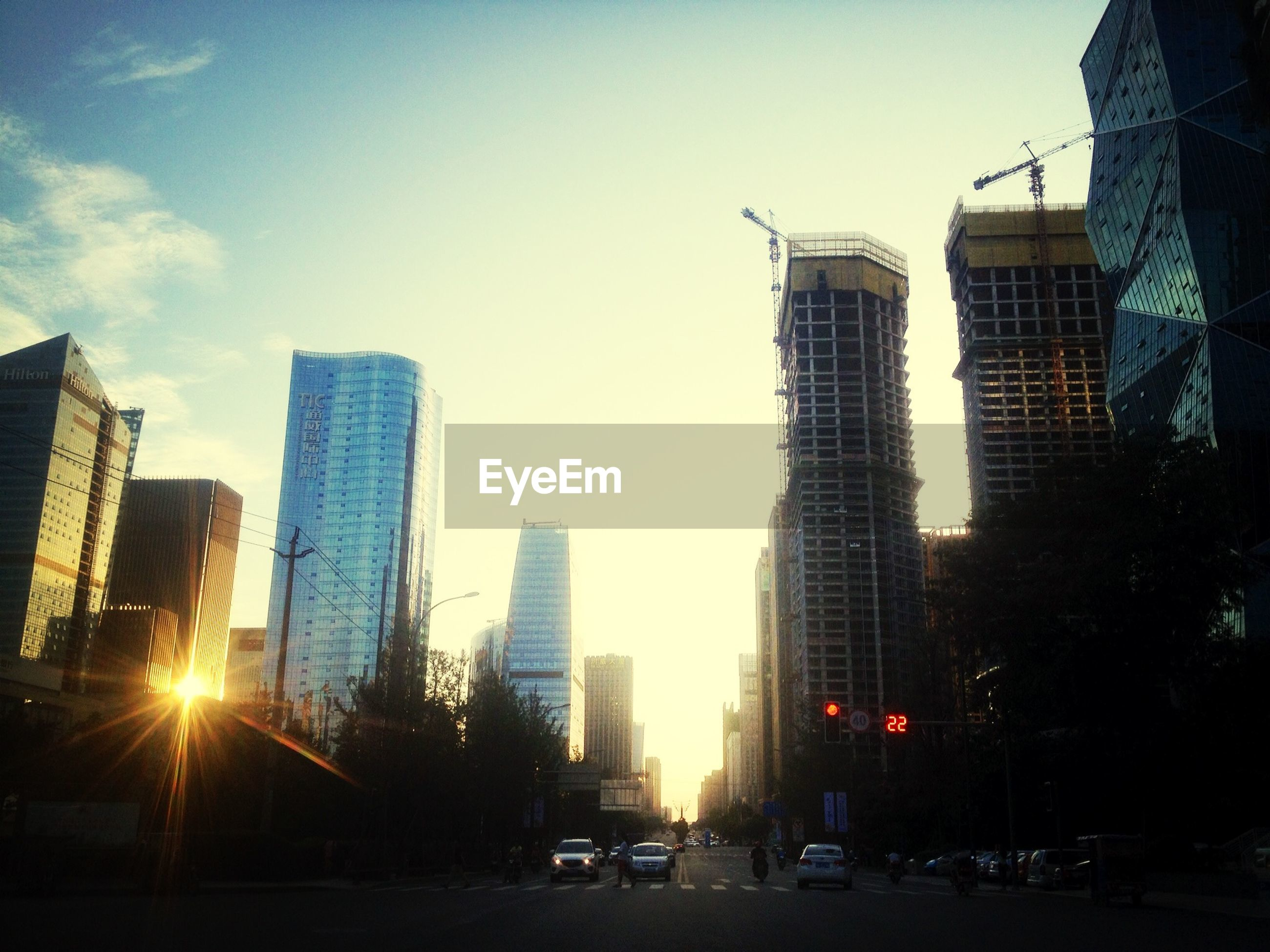 building exterior, architecture, city, built structure, car, transportation, land vehicle, skyscraper, mode of transport, sunset, tall - high, street, office building, tower, modern, sun, sunlight, city life, road, building