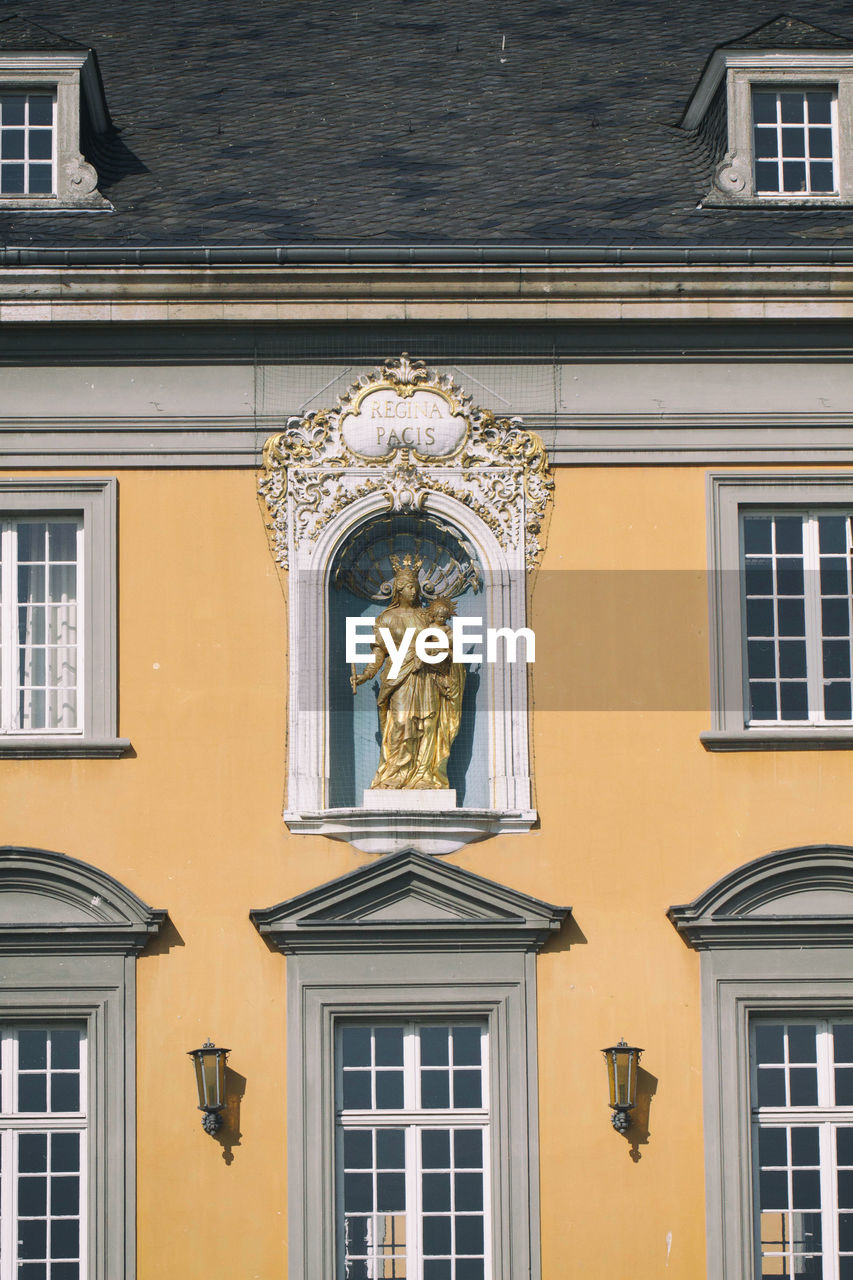built structure, architecture, building exterior, window, building, no people, yellow, human representation, representation, day, low angle view, art and craft, male likeness, outdoors, female likeness, sculpture, residential district, lighting equipment, glass - material, sunlight