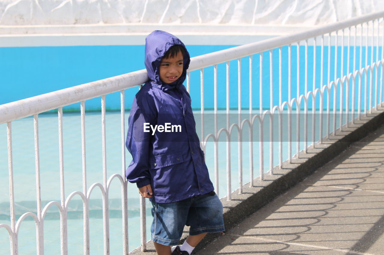 Cute boy wearing raincoat while leaning on railing