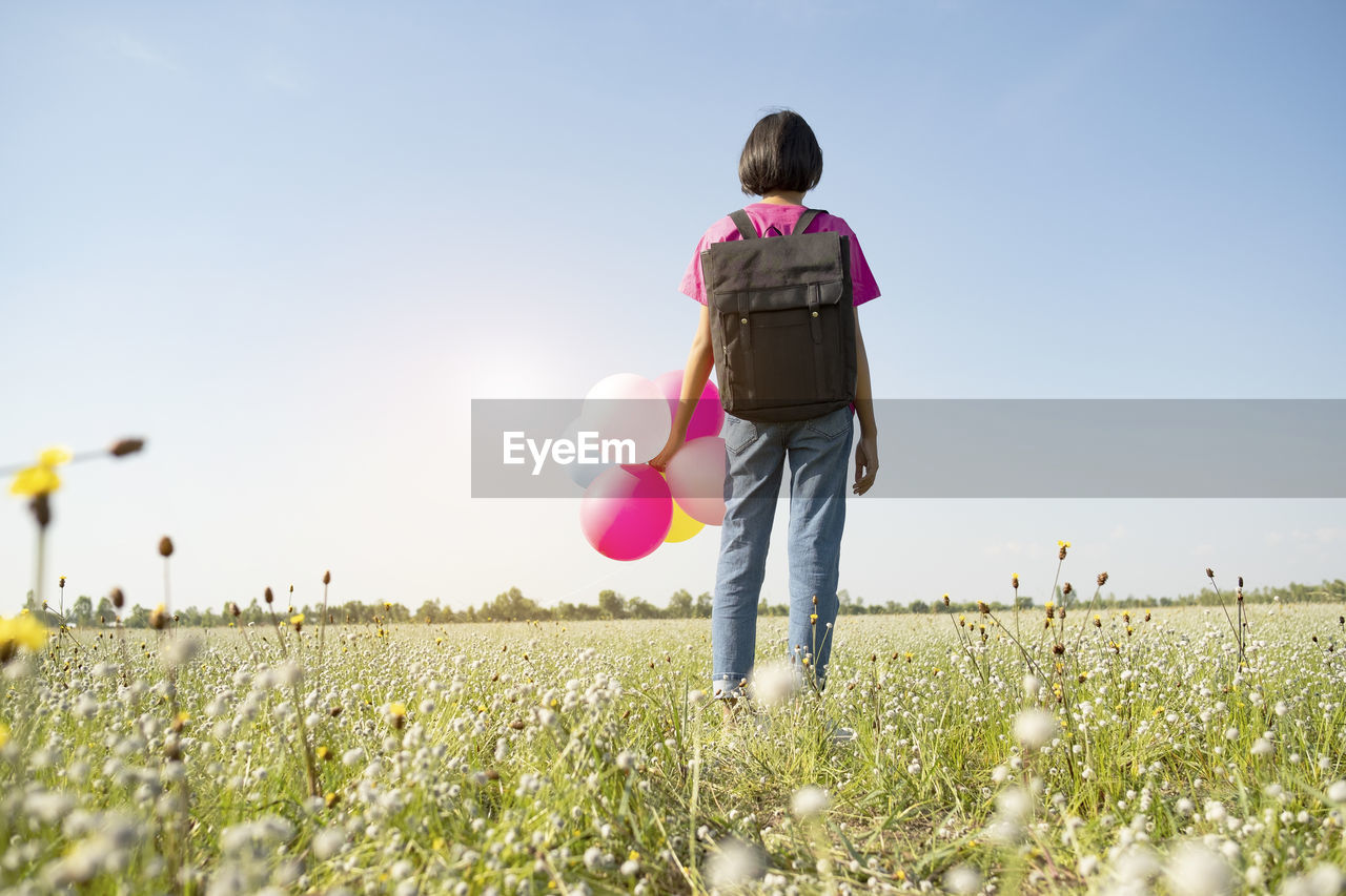 Rear view of girl with balloons on land