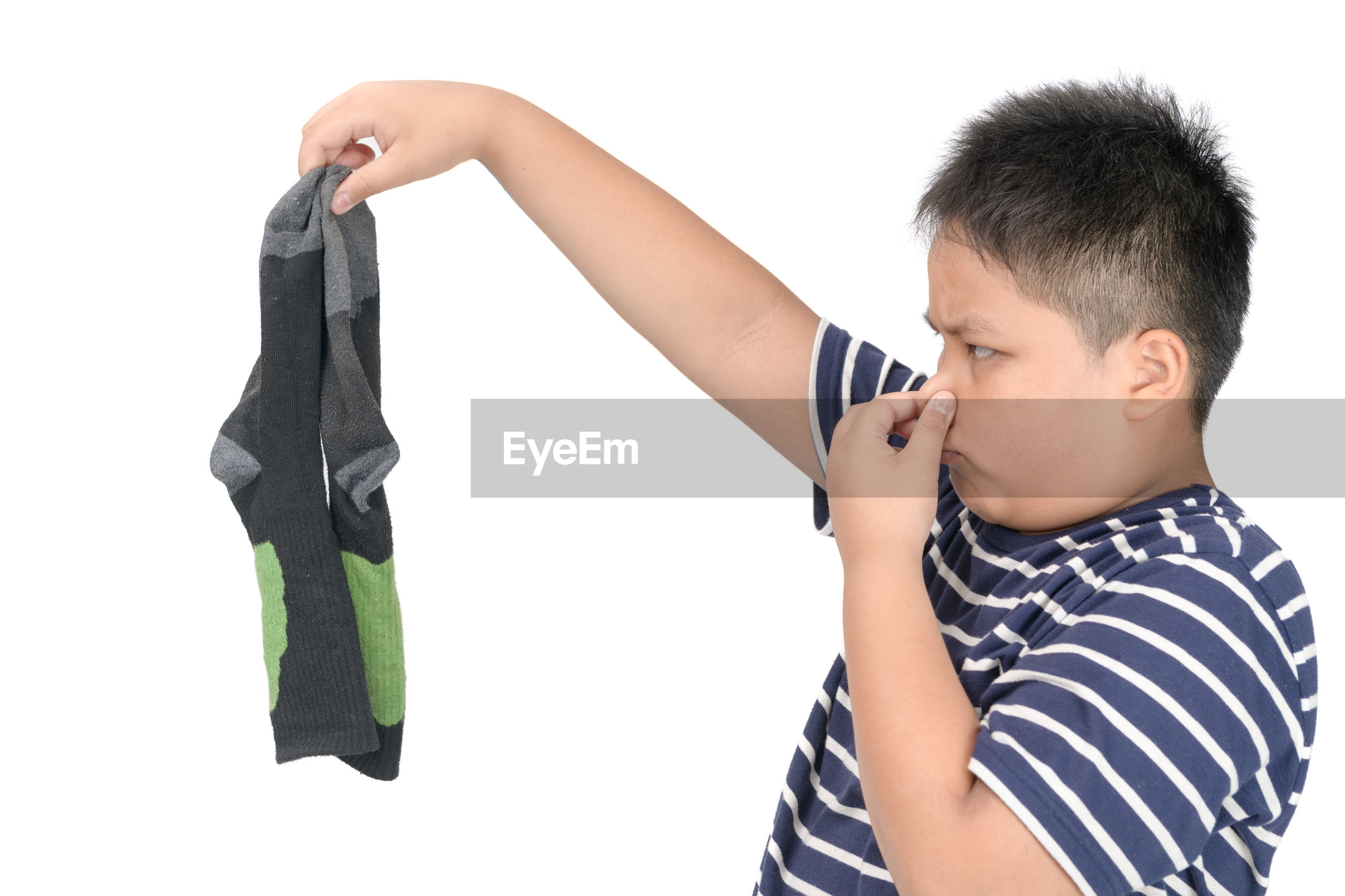 Boy covering nose while holding socks against white background