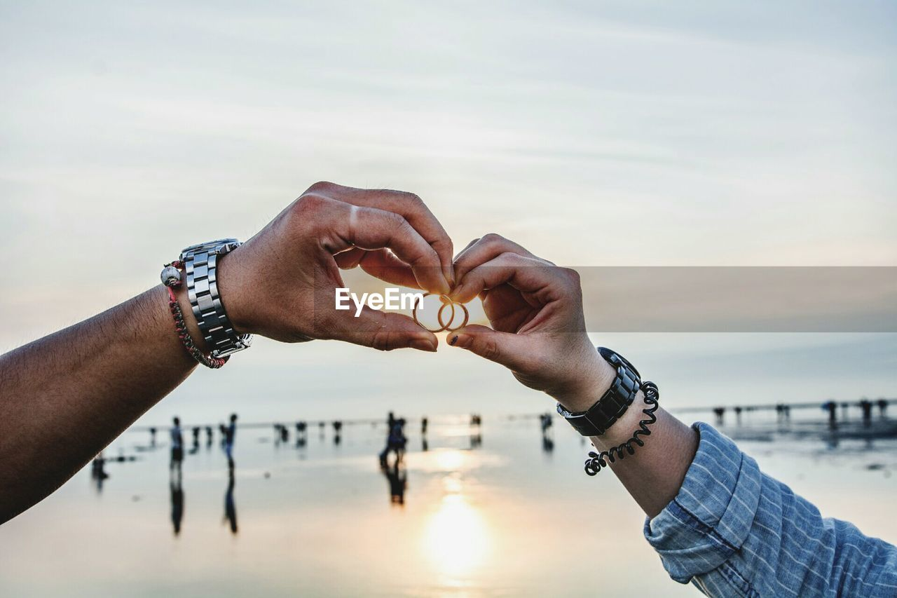 Cropped Image Of Couple Holding Rings At Beach Against Sky