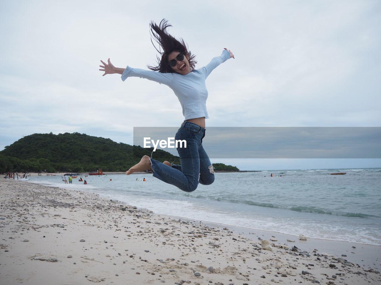 Full length of happy woman jumping at beach