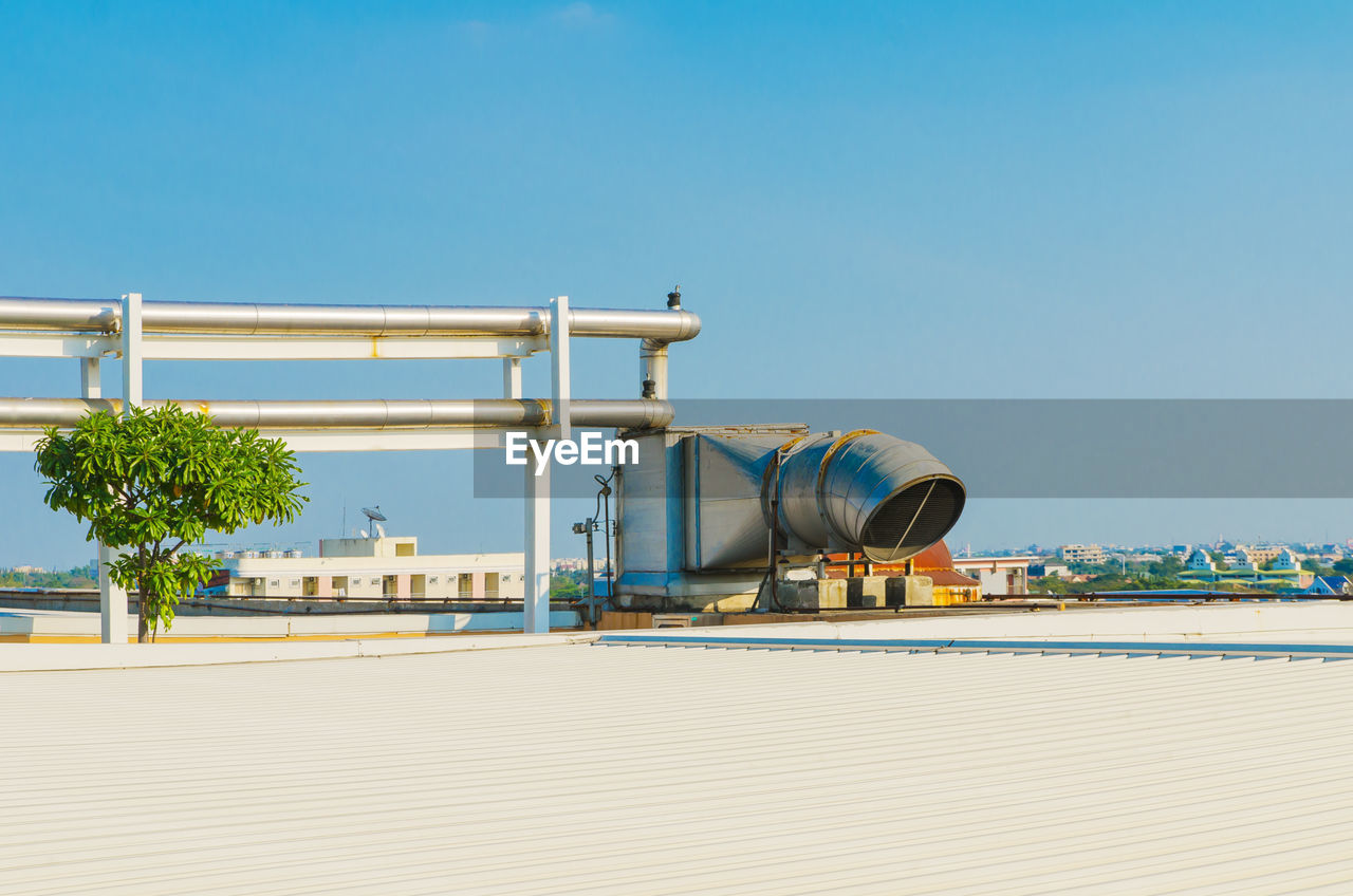 sky, nature, clear sky, built structure, architecture, day, building exterior, industry, copy space, blue, sunlight, outdoors, plant, no people, metal, factory, industrial building, tree, fuel and power generation, storage tank