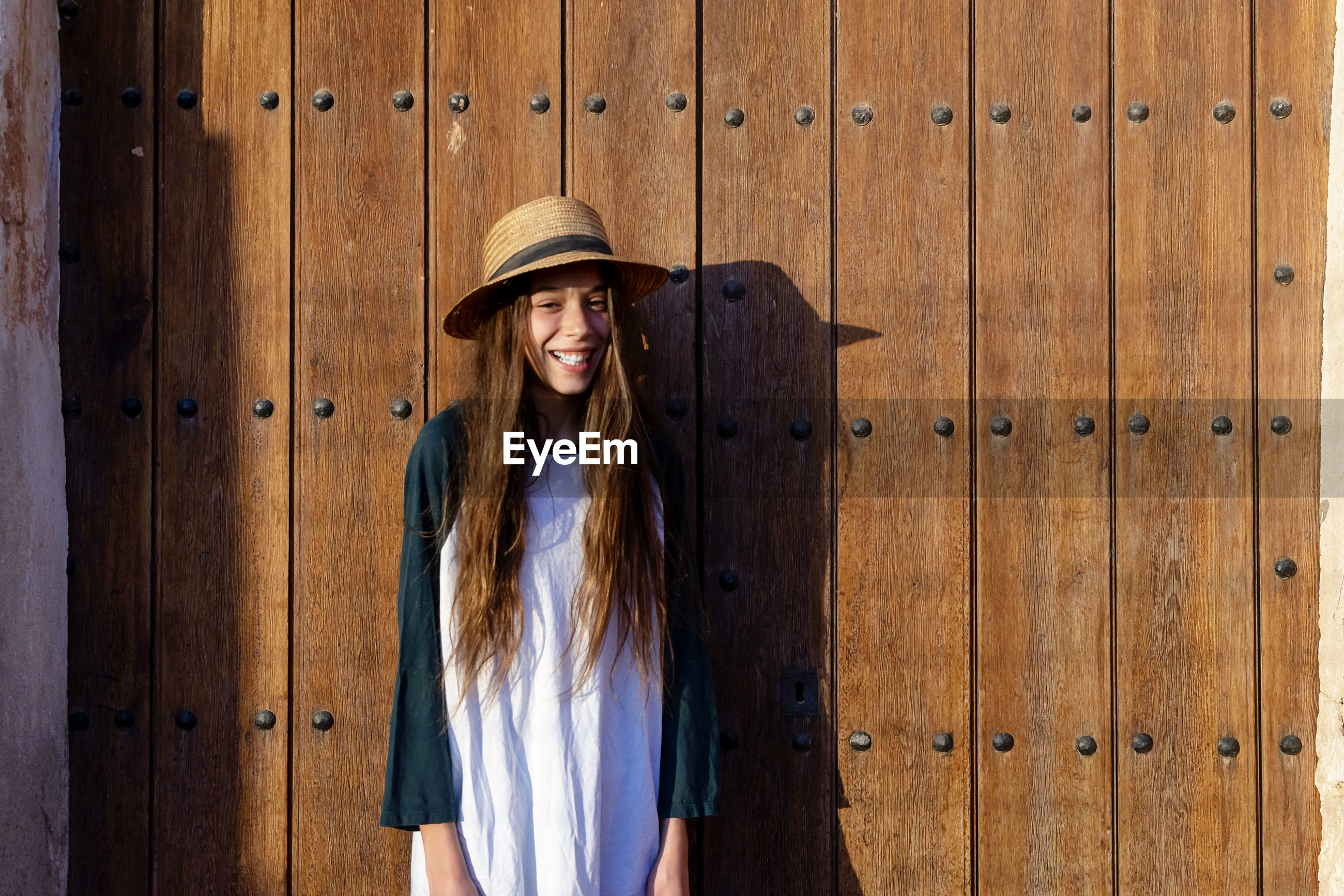 Portrait of young woman wearing hat standing against wooden wall