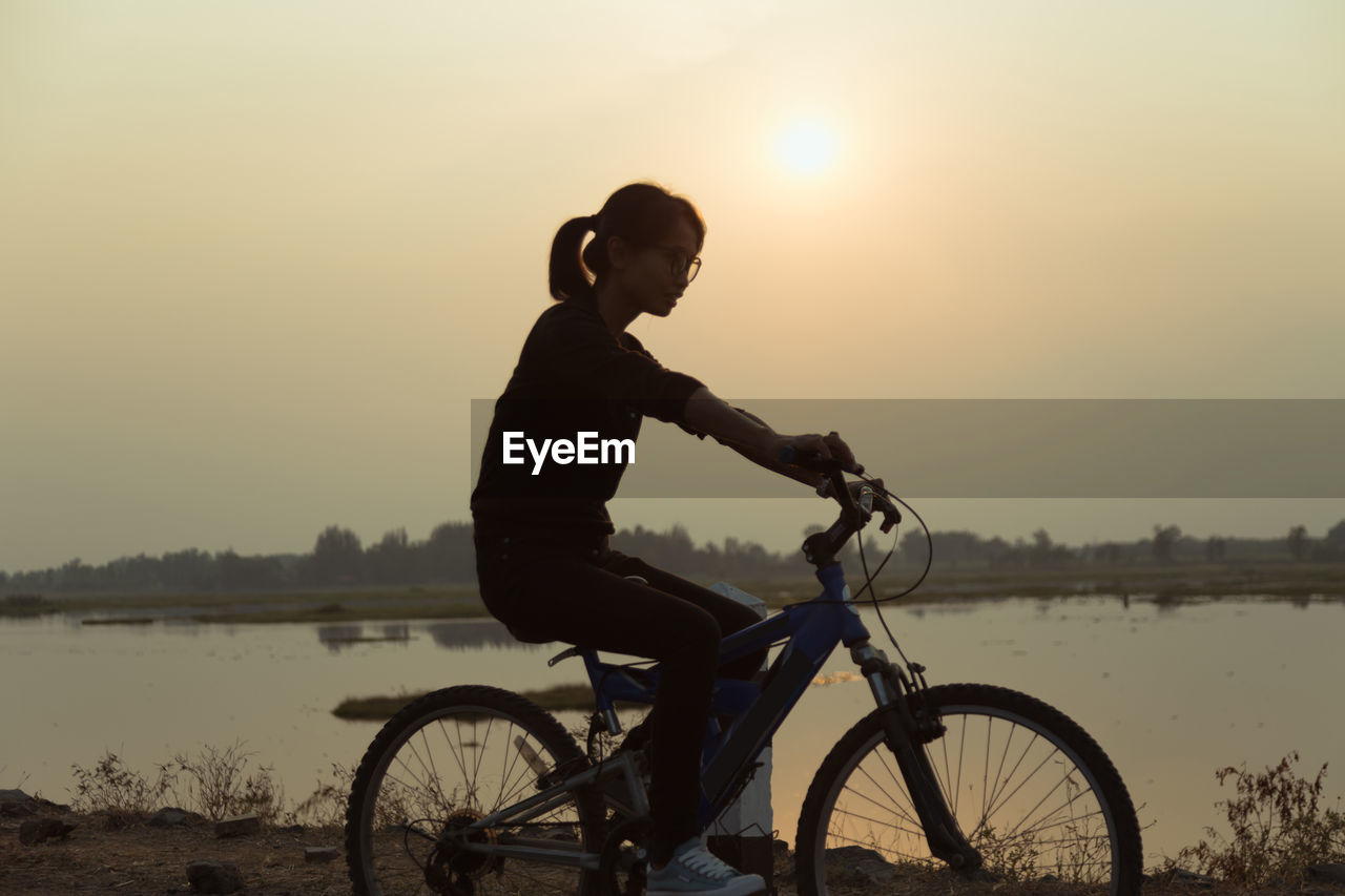 Side view of woman riding bicycle by lake against sky during sunset