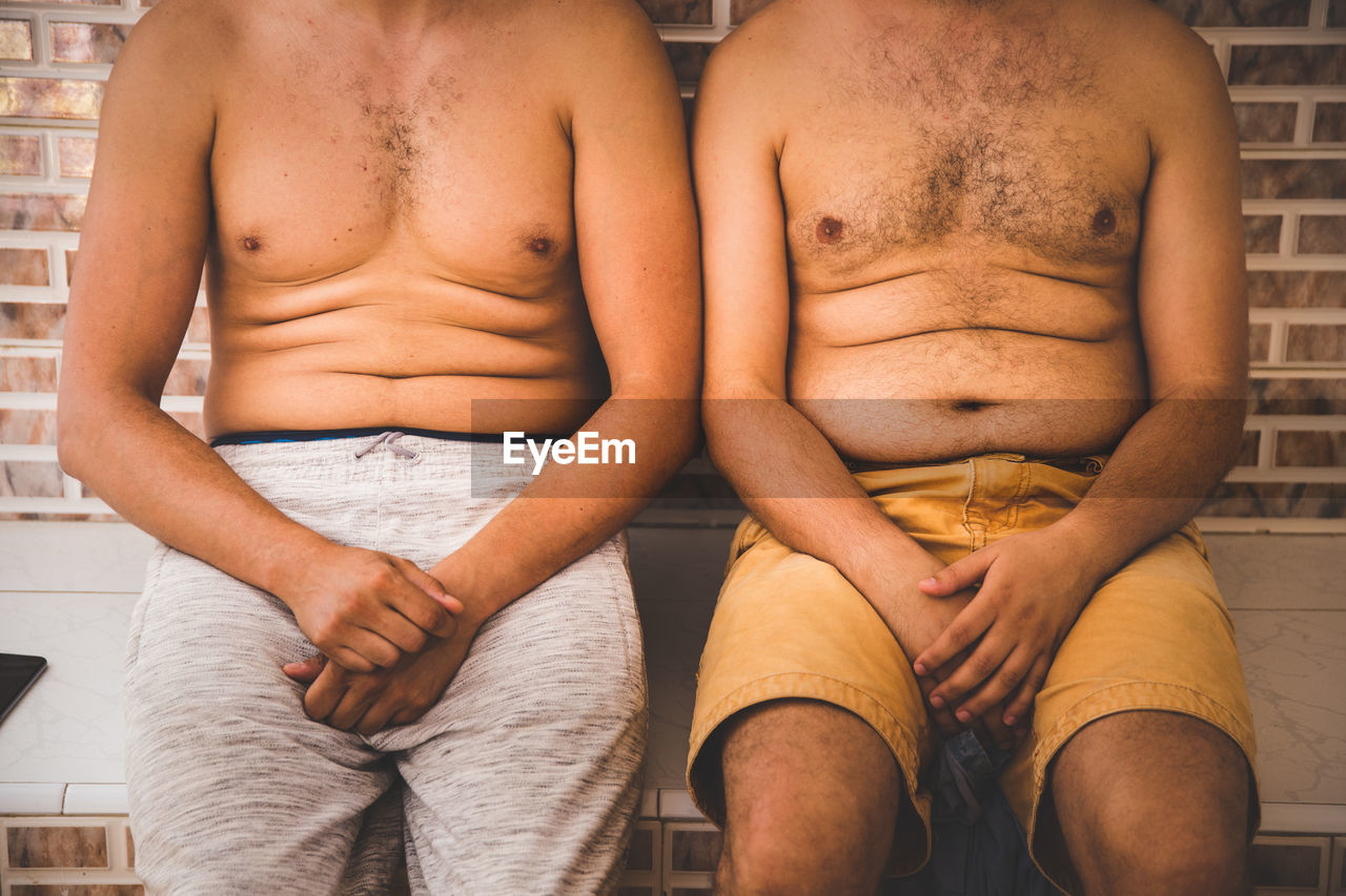 Midsection Of Shirtless Men Sitting Against Wall