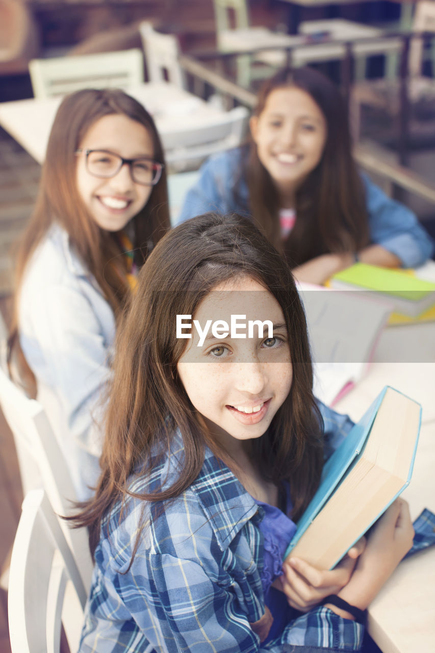 Portrait of smiling teenage friends with books sitting on desk