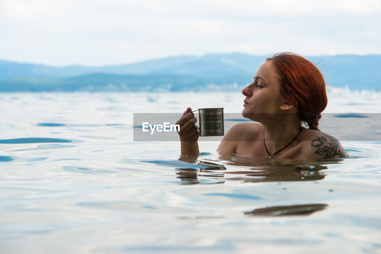Young Woman Having Drink In Sea