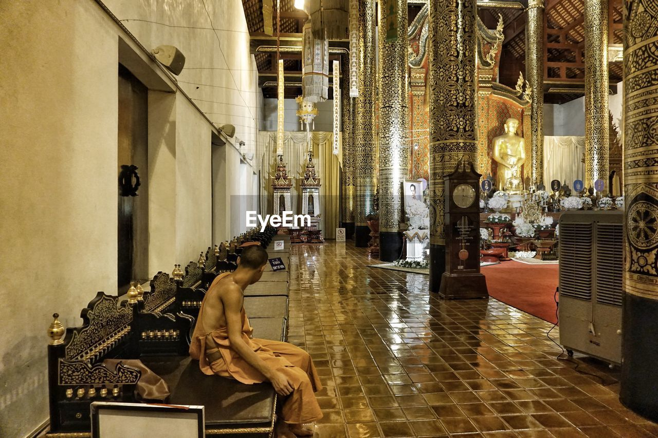 indoors, real people, spirituality, religion, place of worship, one person, sitting, full length, architecture, day, people