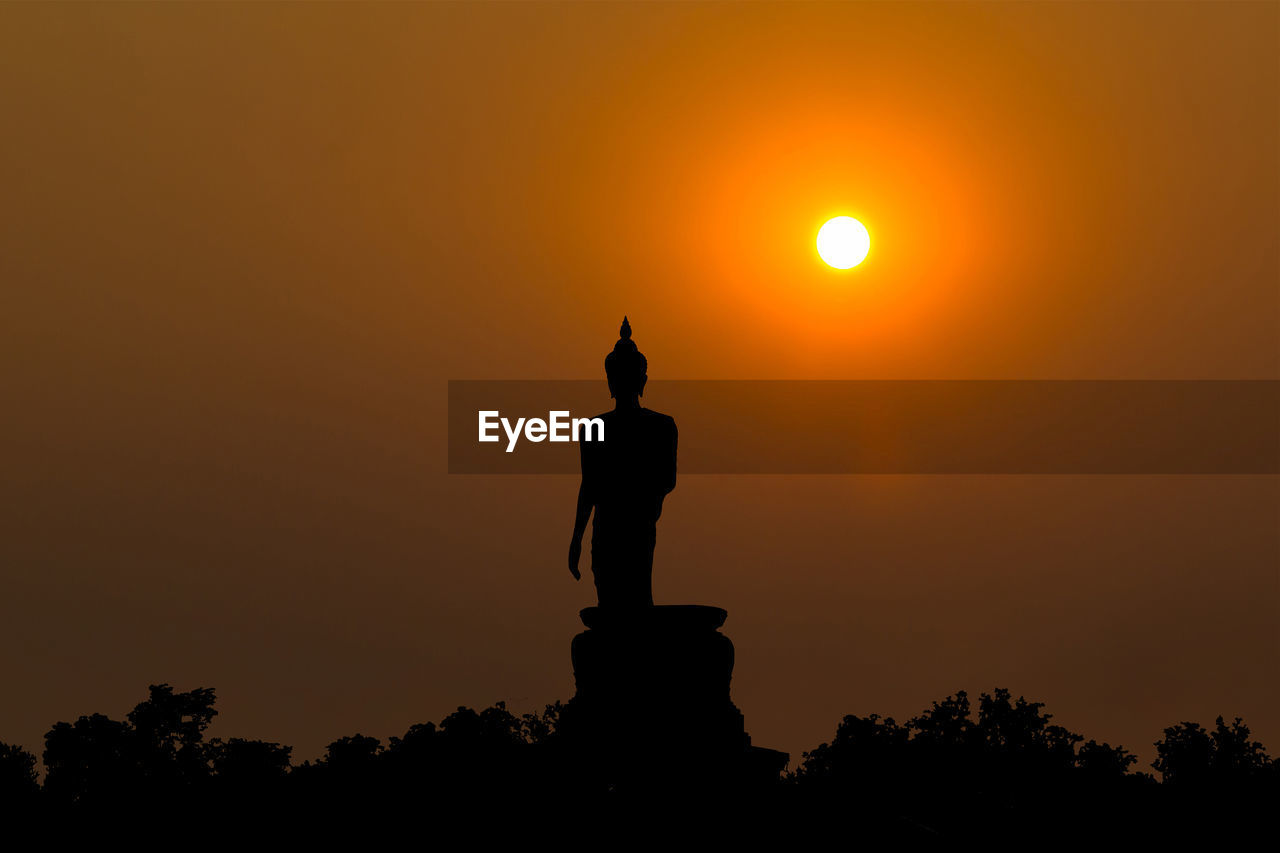 sunset, silhouette, sky, orange color, sun, statue, beauty in nature, sculpture, tree, nature, human representation, scenics - nature, art and craft, representation, religion, low angle view, no people, spirituality, male likeness, place of worship, outdoors