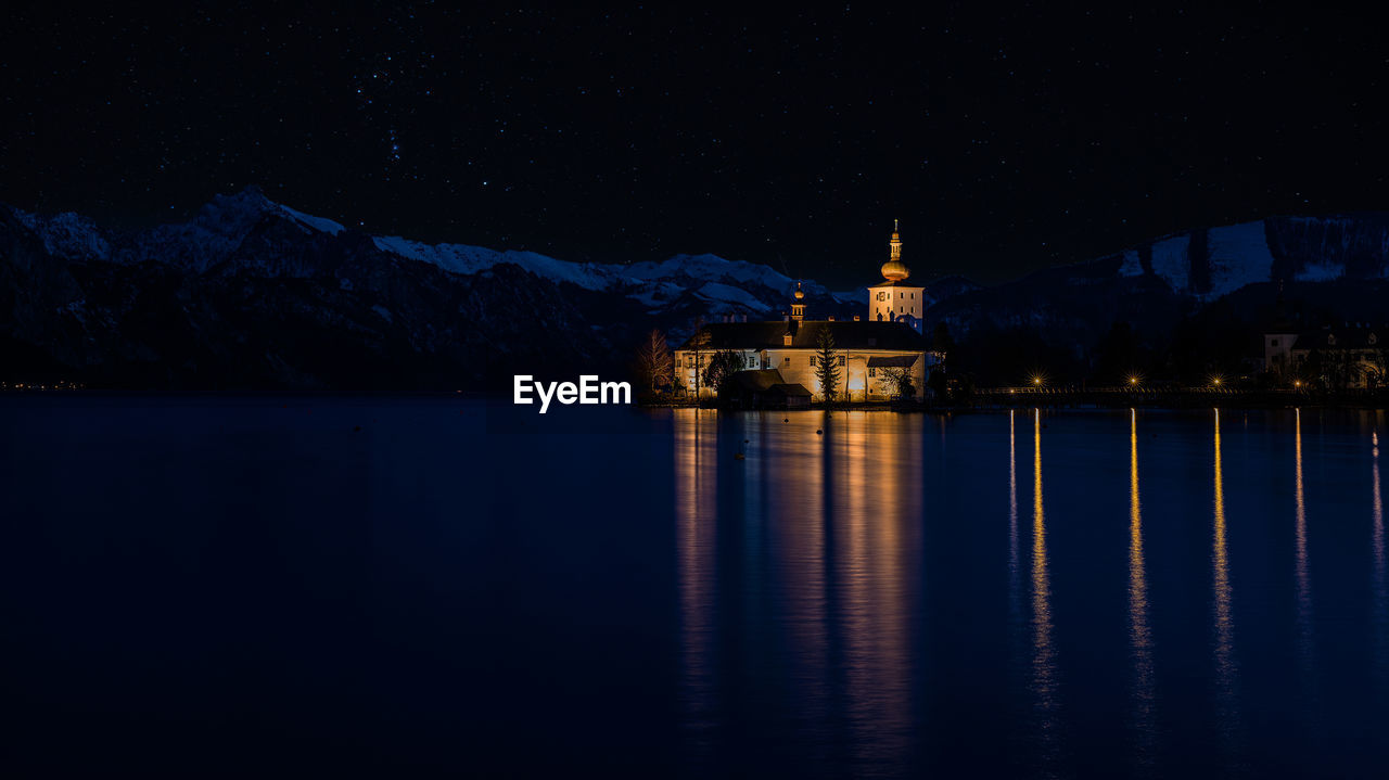 water, night, architecture, reflection, illuminated, sky, building exterior, mountain, waterfront, built structure, no people, beauty in nature, nature, scenics - nature, religion, lake, building, travel destinations, belief, snowcapped mountain