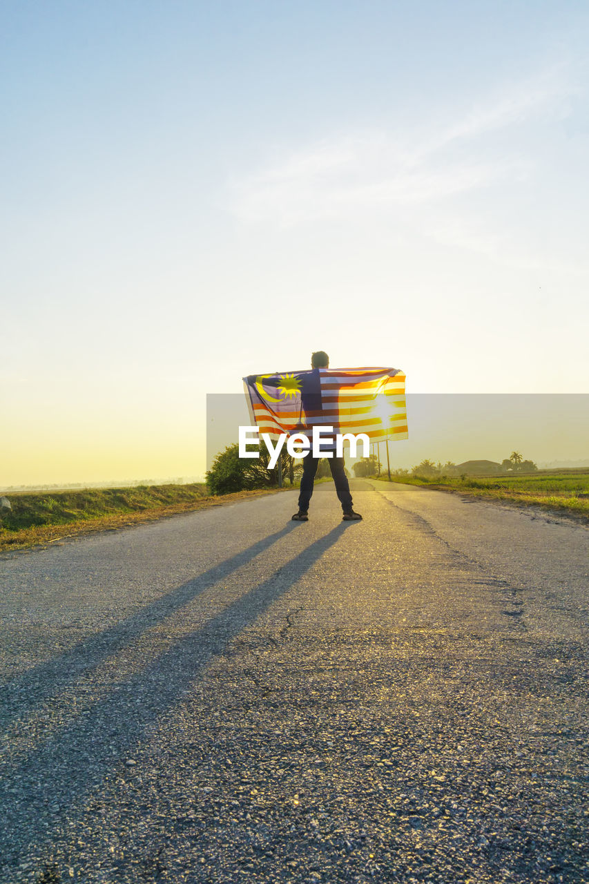 sky, one person, full length, road, sunlight, real people, transportation, rear view, nature, men, direction, day, sunset, the way forward, lifestyles, sun, standing, outdoors, field, lens flare, uniform
