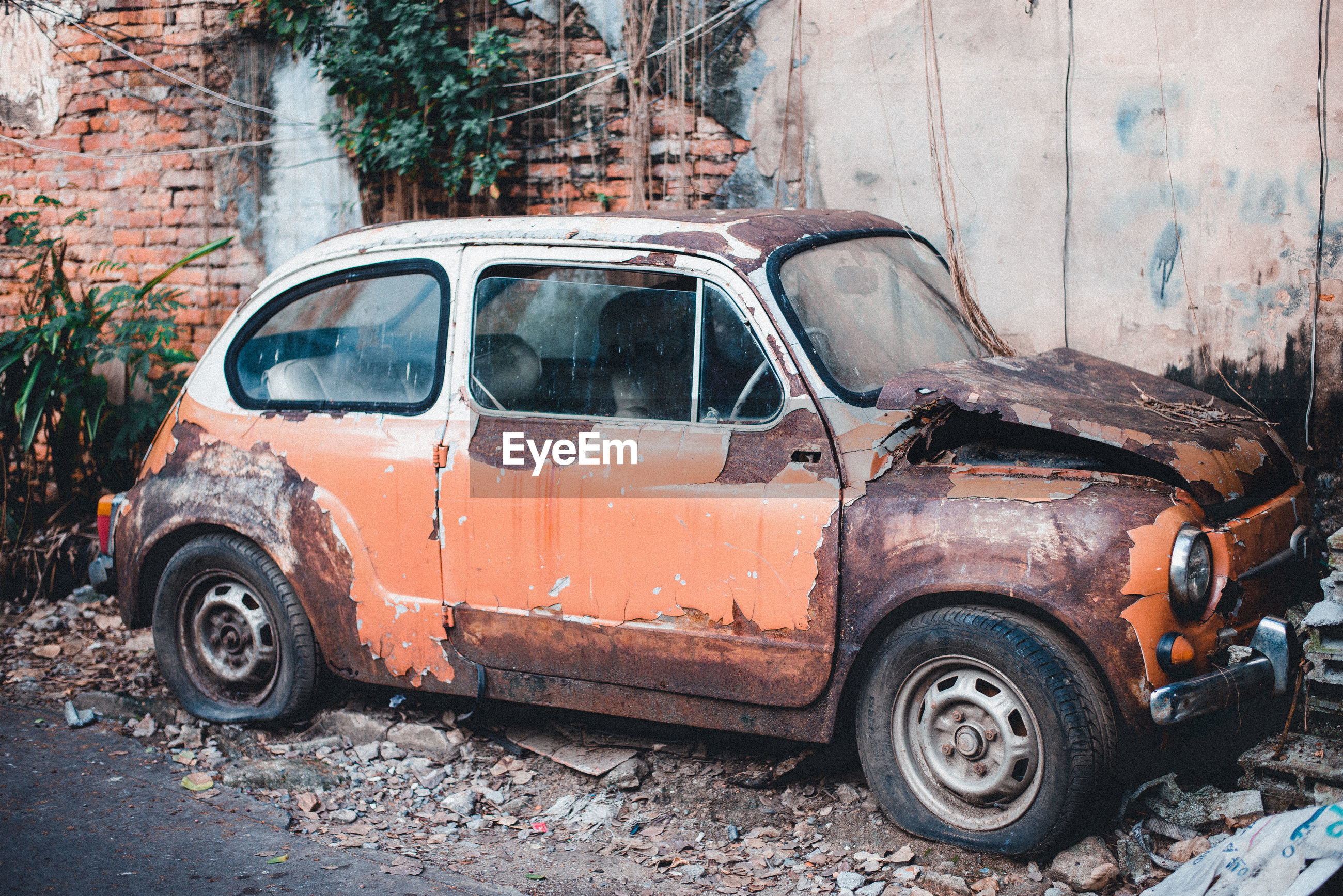 Abandoned car against wall