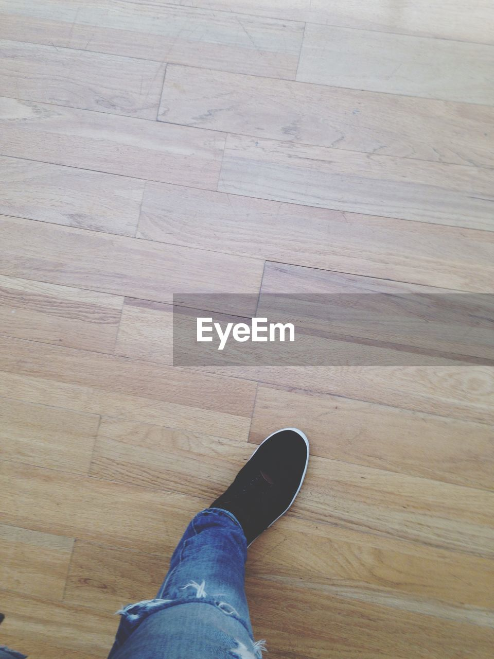 Low section of woman walking on wooden floor