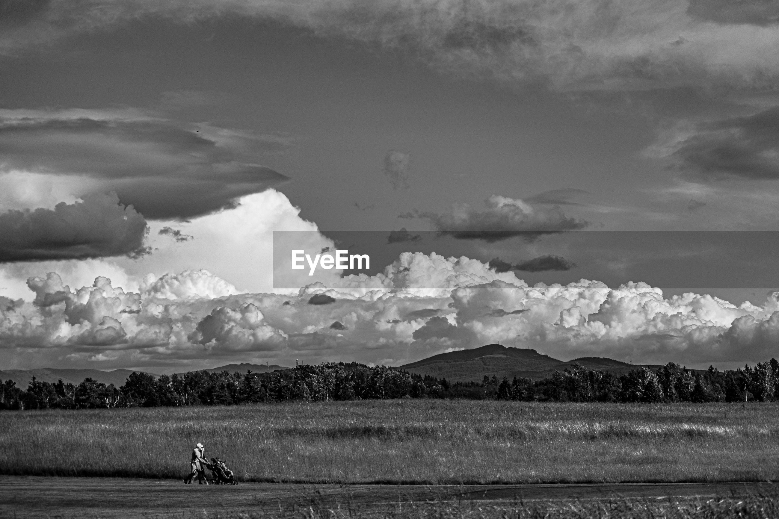 cloud - sky, sky, scenics - nature, beauty in nature, tranquil scene, day, mountain, real people, landscape, tranquility, nature, one person, environment, field, non-urban scene, land, water, outdoors, mountain range
