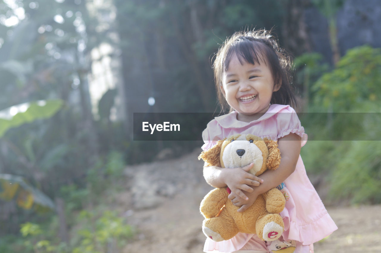 Cute Girl Holding Teddy Bear While Standing Outdoors