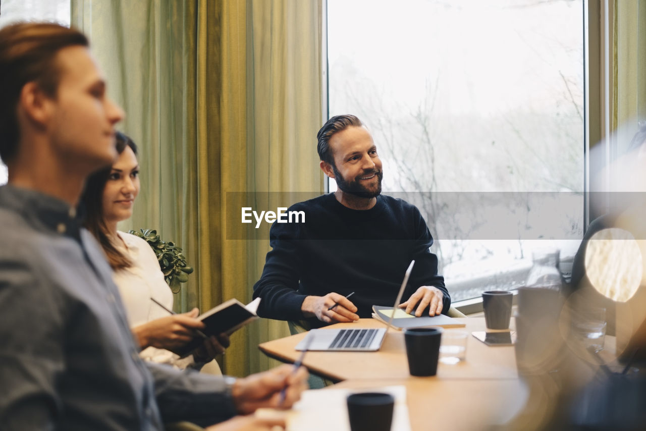 office, business, real people, indoors, smiling, adult, table, men, young adult, selective focus, sitting, young men, meeting, women, males, window, communication, professional occupation, businessman, teamwork, coworker
