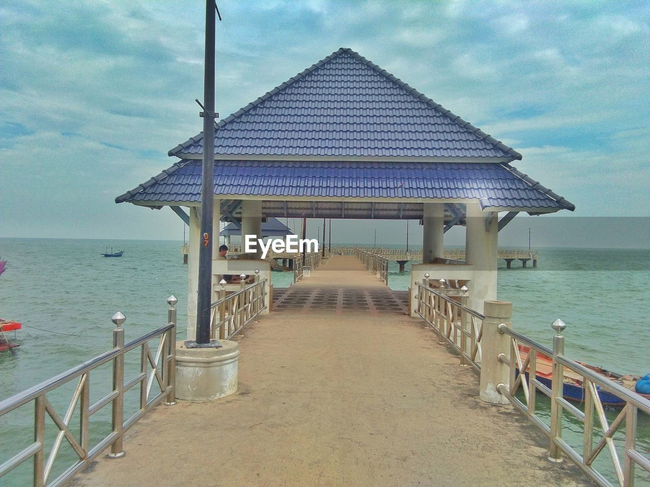architecture, sky, sea, railing, water, built structure, gazebo, the way forward, cloud - sky, horizon, direction, horizon over water, nature, tranquility, pier, tranquil scene, no people, land, beach, diminishing perspective, outdoors, architectural column