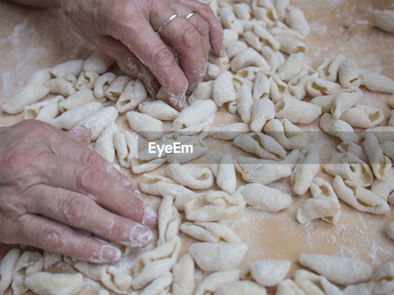 Cropped Hands Making Pasta On Wooden Table
