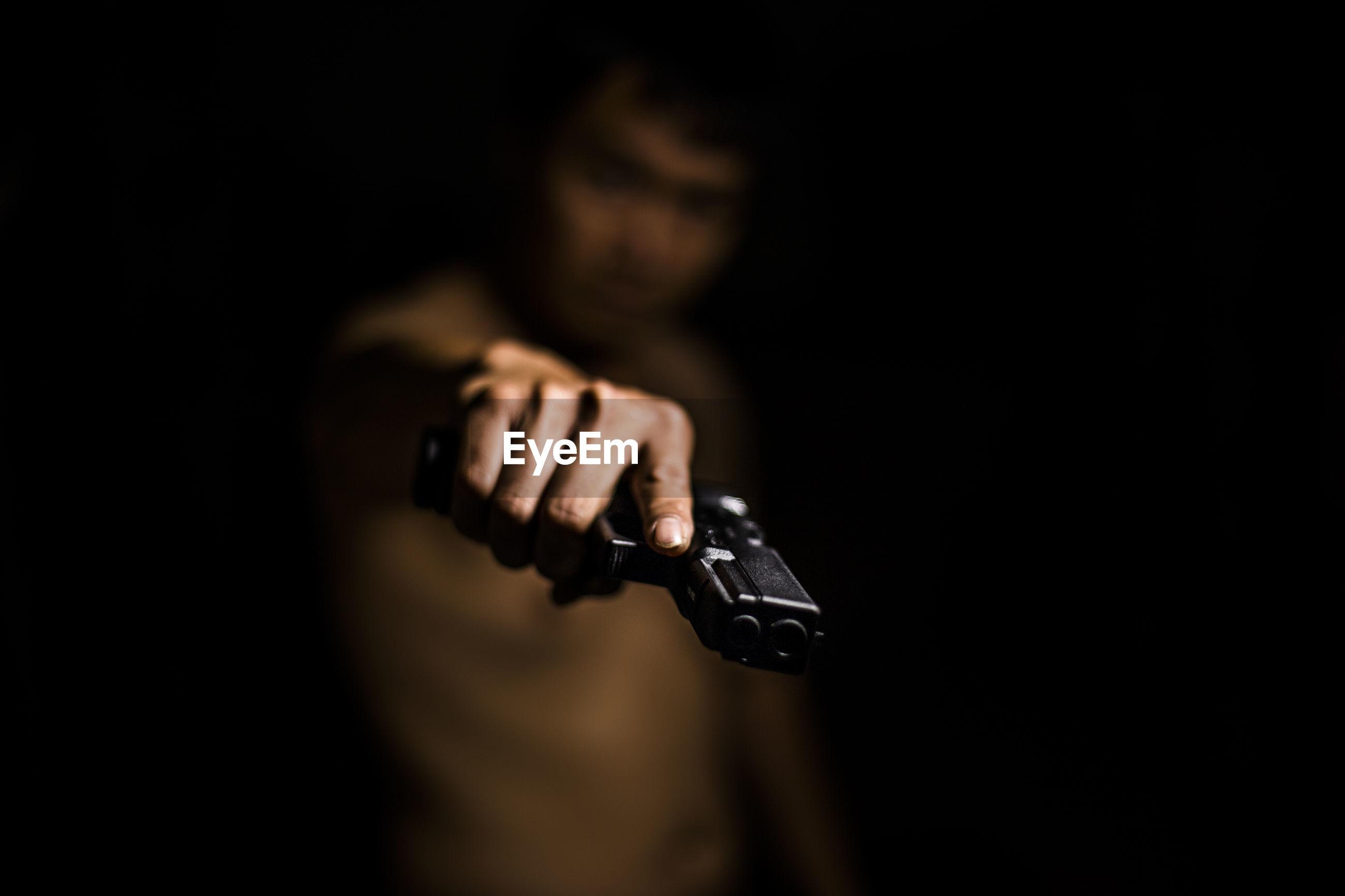 Shirtless man aiming gun against black background