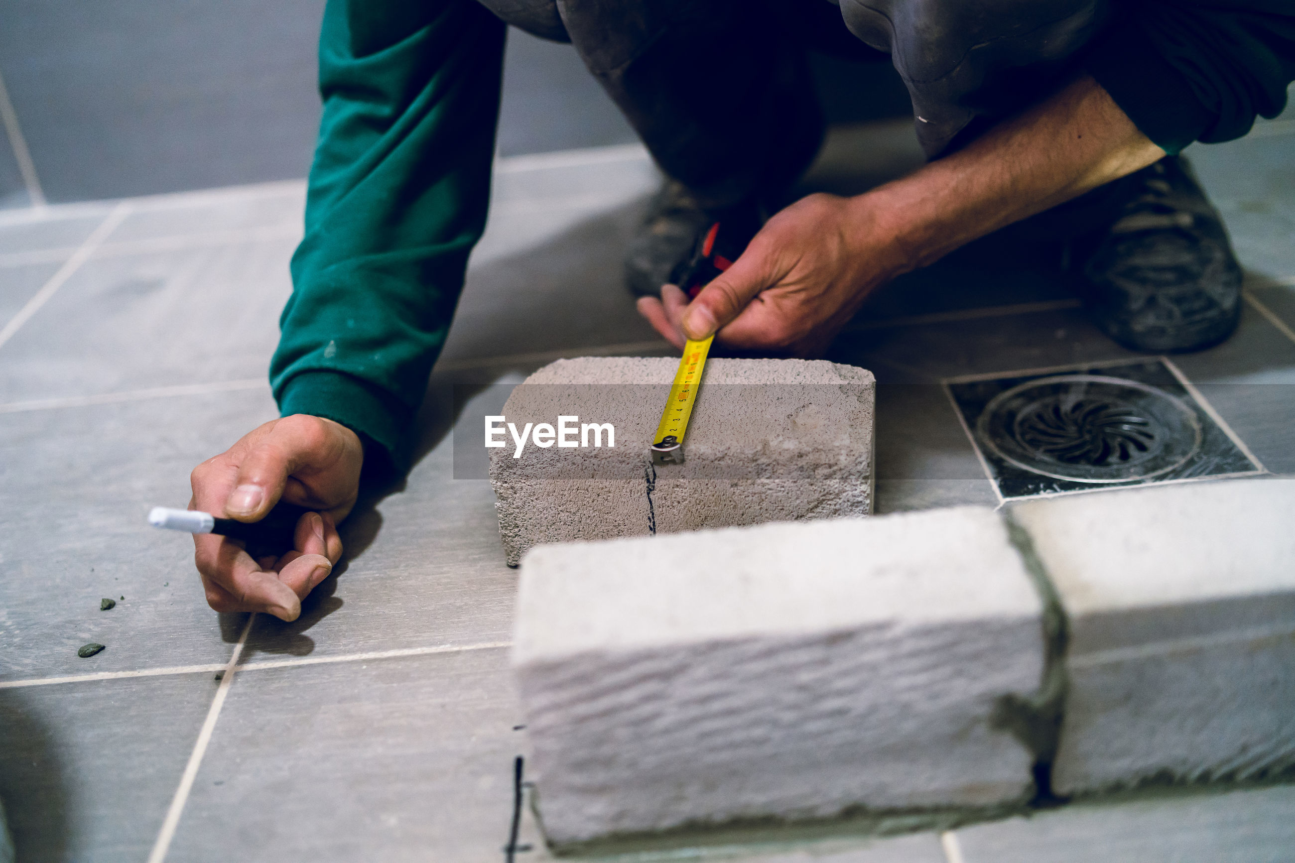 Low section of male worker measuring brick on floor