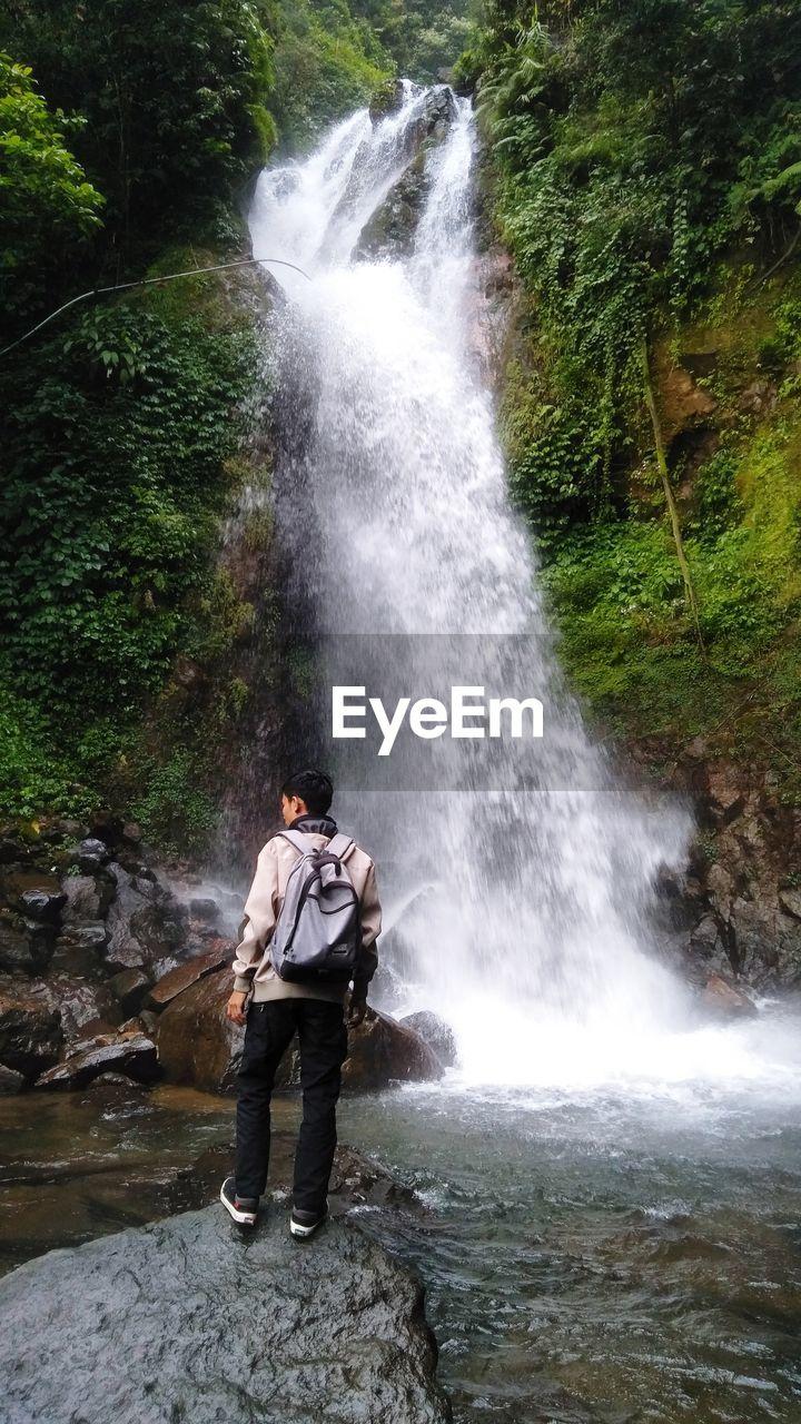Hiker standing against waterfall