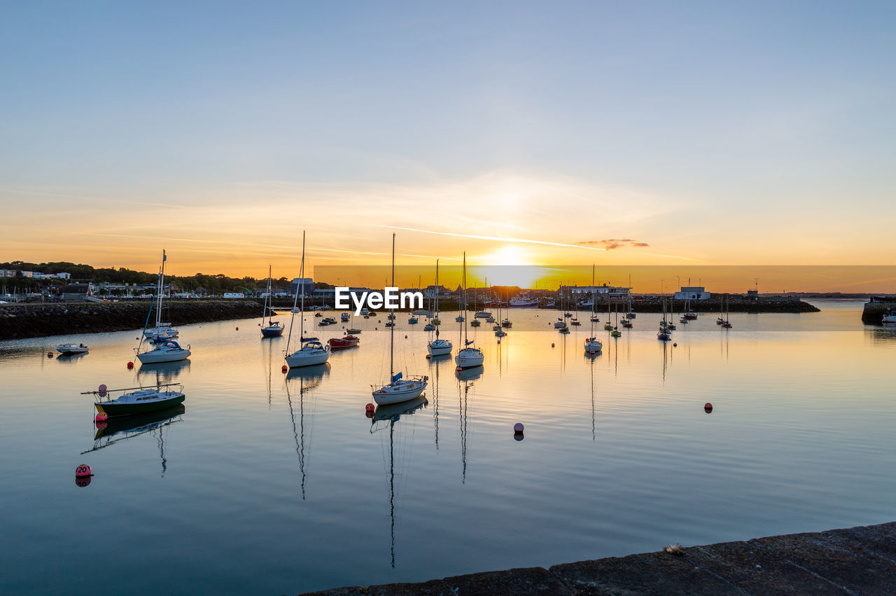 water, sunset, nautical vessel, sky, transportation, mode of transportation, moored, reflection, beauty in nature, nature, sailboat, scenics - nature, sea, orange color, tranquility, no people, tranquil scene, cloud - sky, harbor, outdoors, marina, yacht, wooden post, port