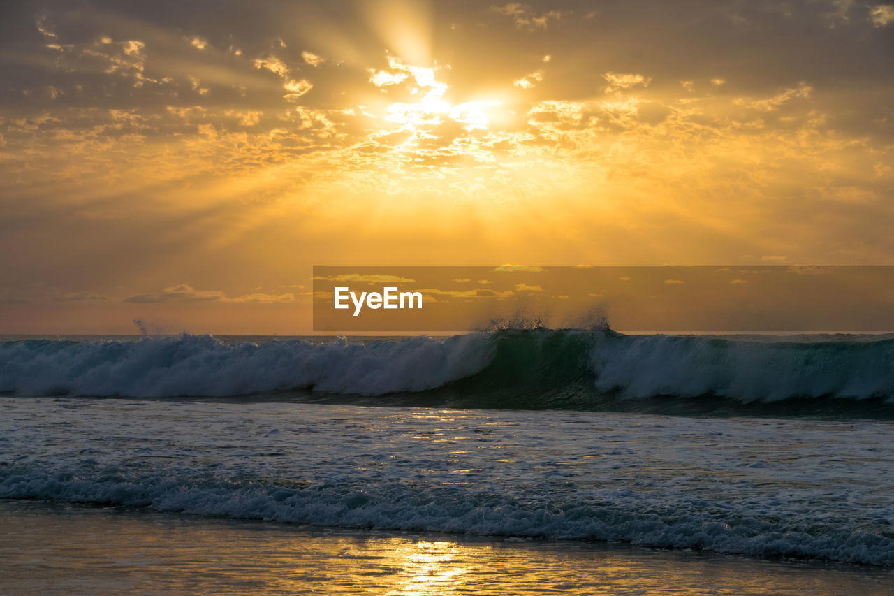 Scenic View Of Waves Splashing In Sea Against Sky During Sunset