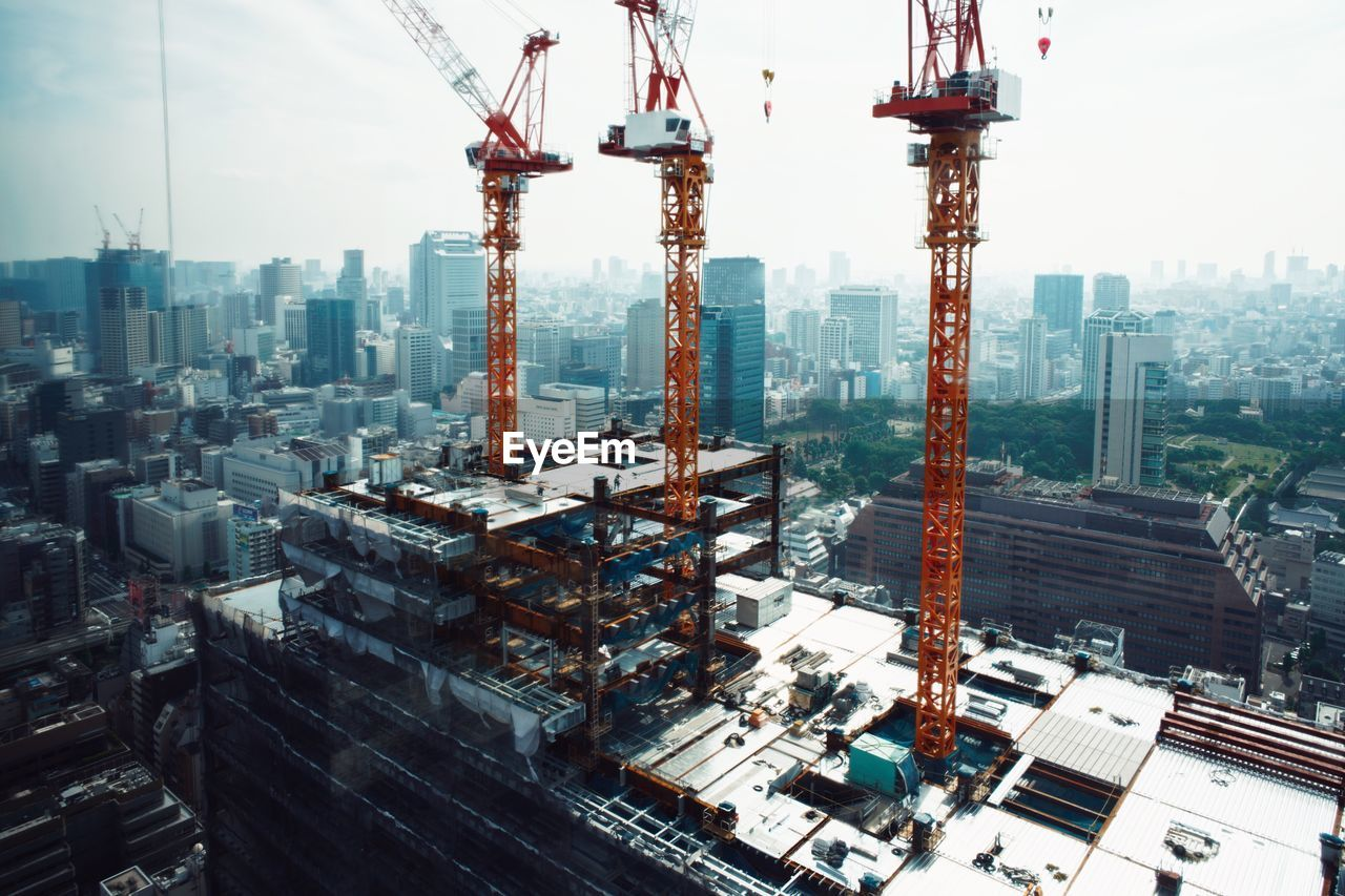 building exterior, architecture, built structure, city, machinery, cityscape, industry, crane - construction machinery, development, office building exterior, construction industry, sky, building, skyscraper, tall - high, nature, day, construction site, no people, outdoors, modern, construction equipment
