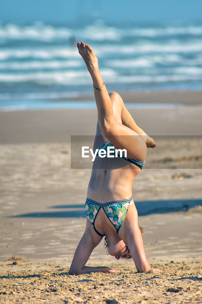 sea, water, beach, land, full length, real people, lifestyles, one person, sand, clothing, leisure activity, exercising, nature, swimwear, healthy lifestyle, day, beauty in nature, balance, handstand, outdoors