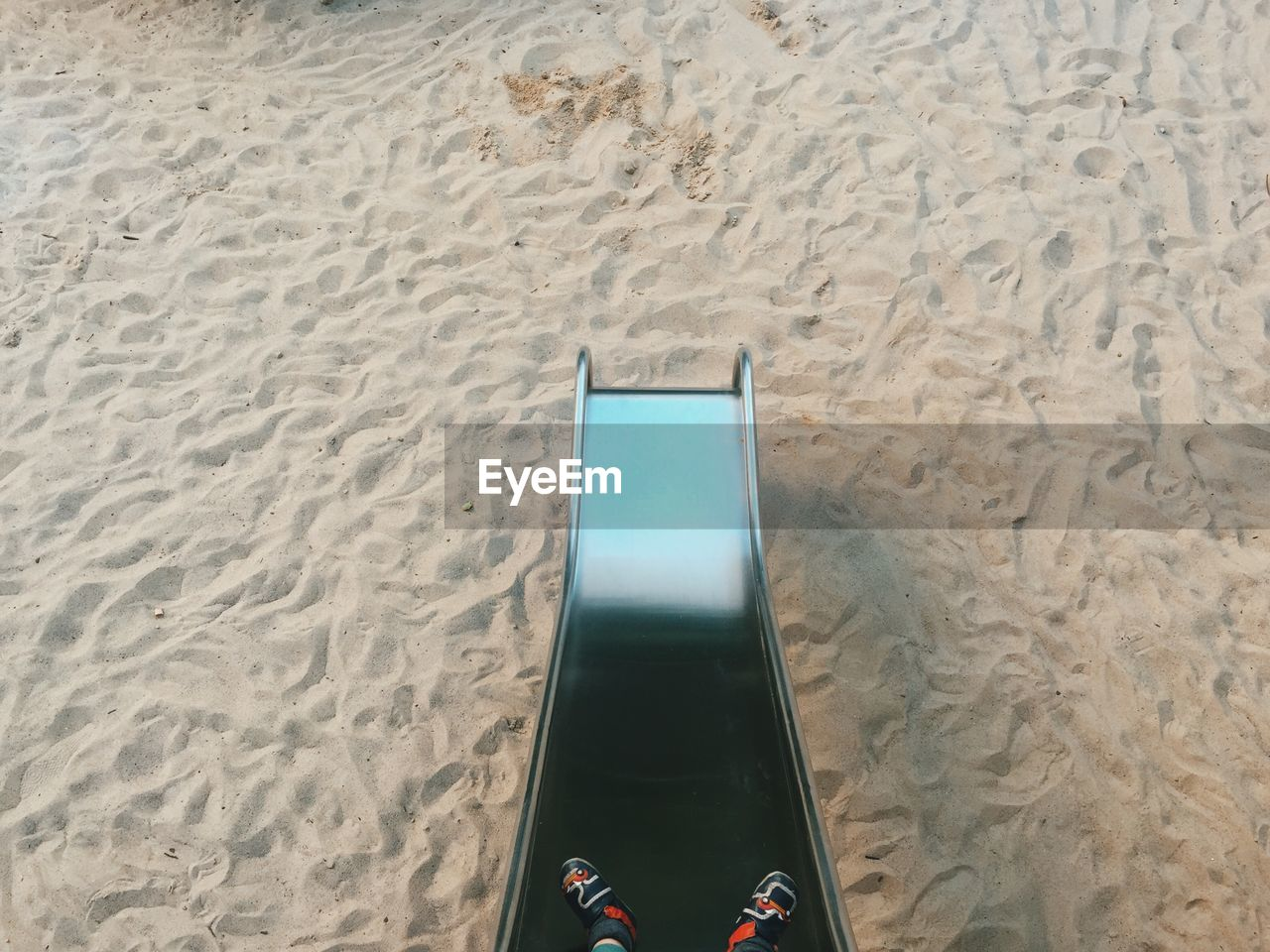 Low section of child sliding from slide at playground
