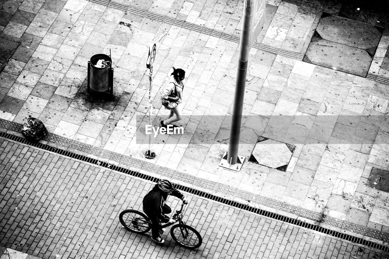 city, real people, high angle view, bicycle, transportation, men, street, people, walking, footpath, mode of transportation, land vehicle, lifestyles, women, two people, adult, city life, travel, day, outdoors, paving stone, waiting, tiled floor