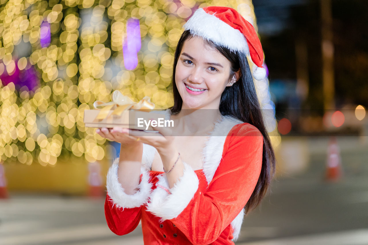 Portrait of smiling young woman wearing santa hat holding gift box outdoors at night