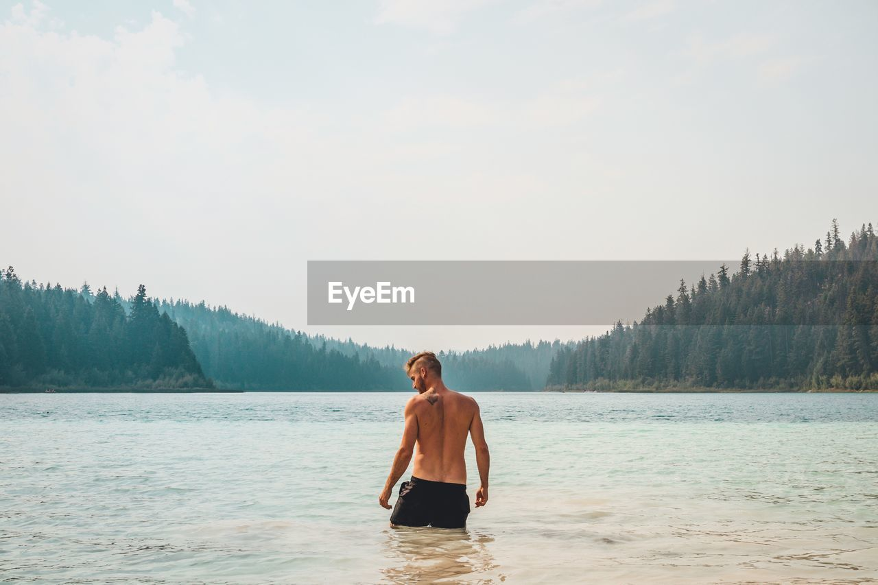 Shirtless Man Standing In Lake Against Clear Sky