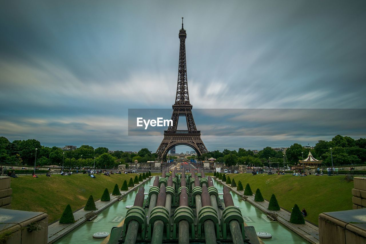 Eiffel tower in city against cloudy sky