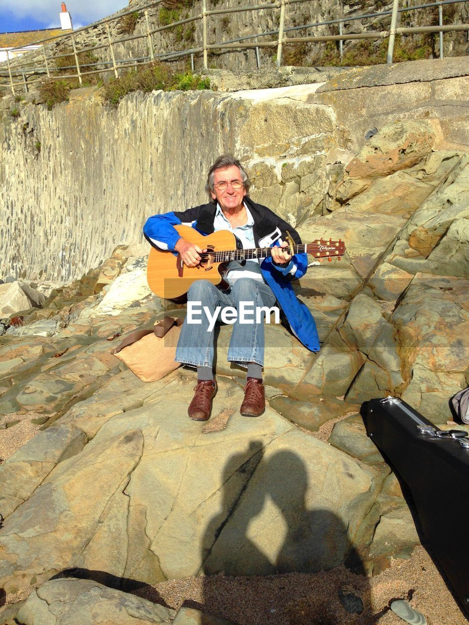 Portrait Of Mature Man Playing Guitar While Sitting On Rock At Beach