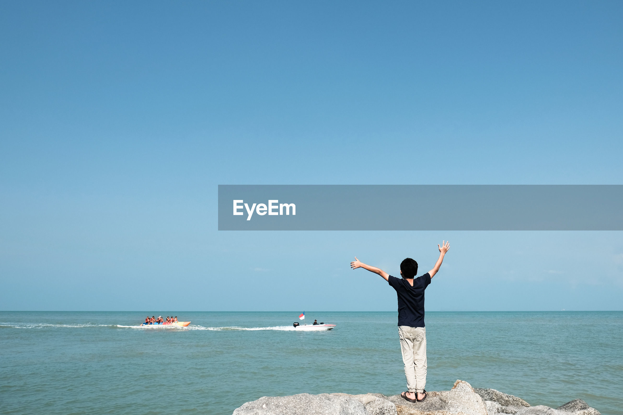 Rear view of boy standing on rock at beach against clear sky