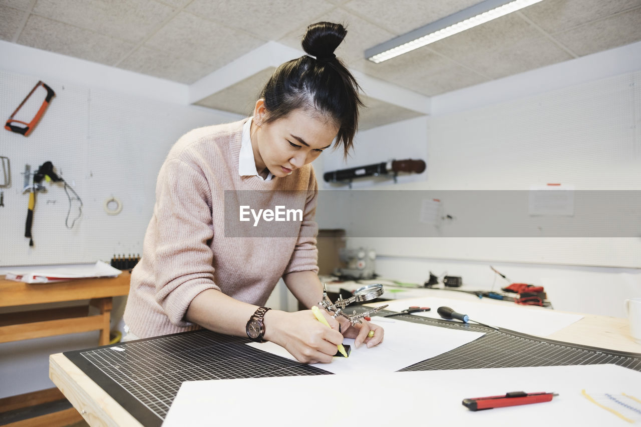 indoors, real people, one person, waist up, table, casual clothing, concentration, publication, looking down, front view, book, holding, women, looking, creativity, adult, standing, writing, young women, hairstyle, design professional