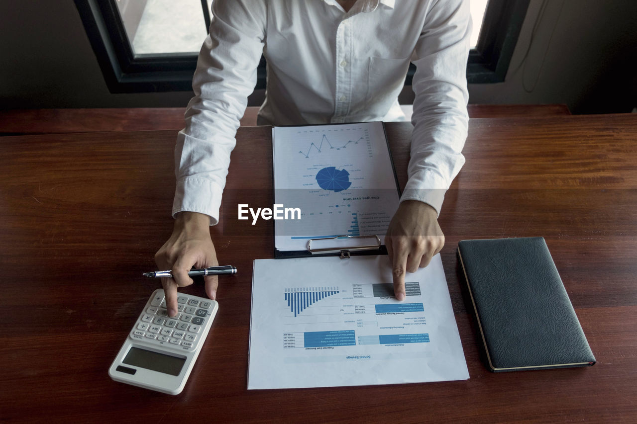 Midsection of man analyzing chart with calculator while sitting at office desk