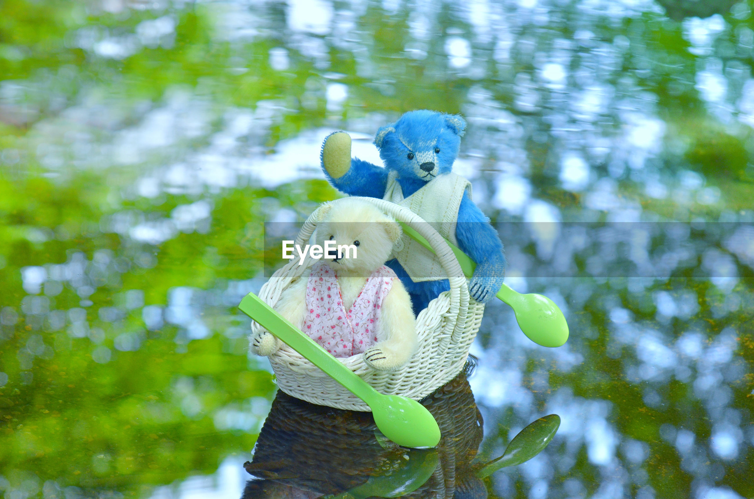 Close-up of stuffed toys in basket over lake