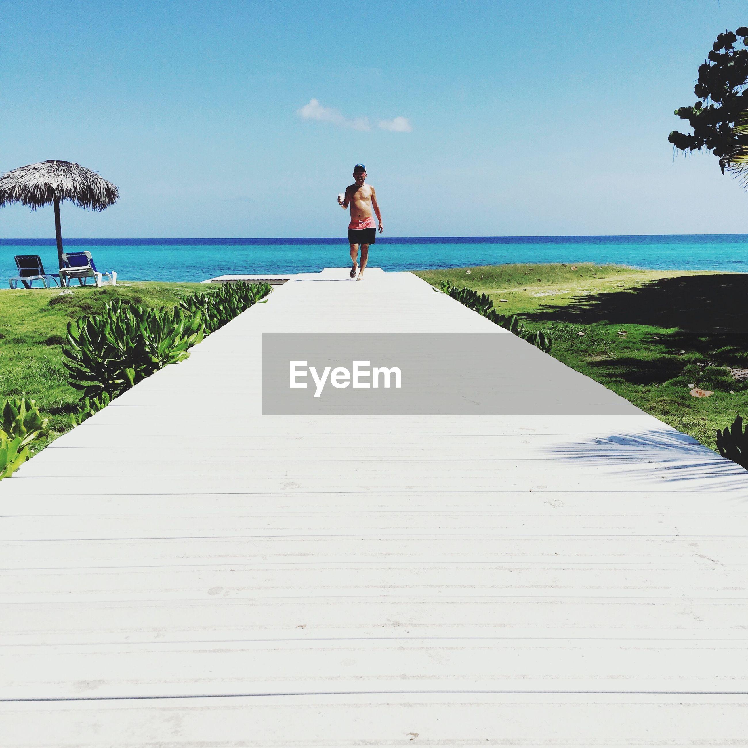 Man walking on pier against clear sky