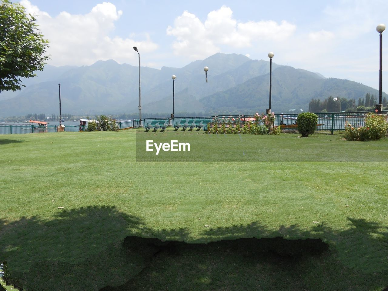 mountain, field, grass, sky, green color, scenics, nature, day, beauty in nature, landscape, no people, tranquility, tranquil scene, mountain range, outdoors, growth, tree, soccer field, playing field, sport, goal post, golf course