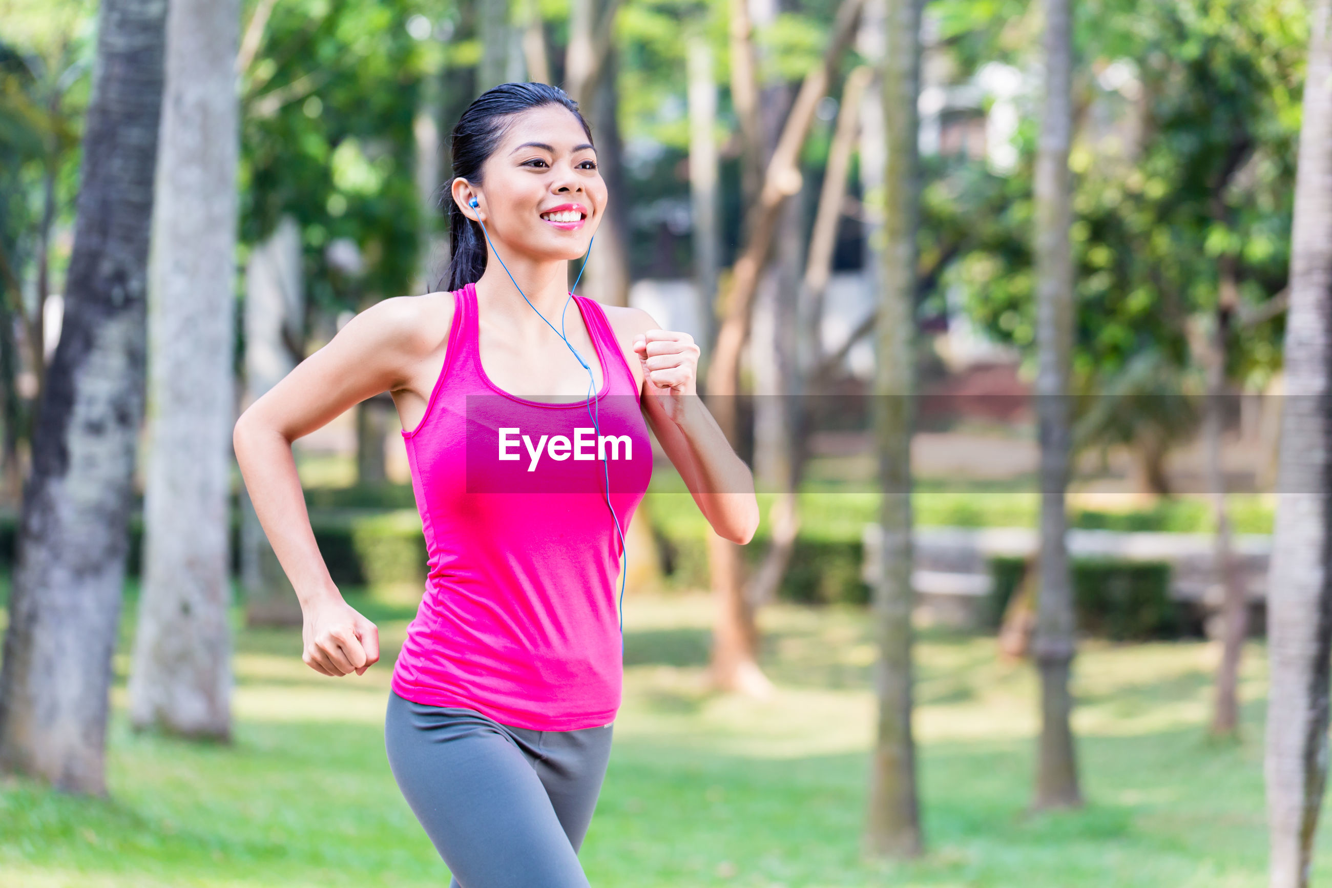 Smiling female athlete exercising in park