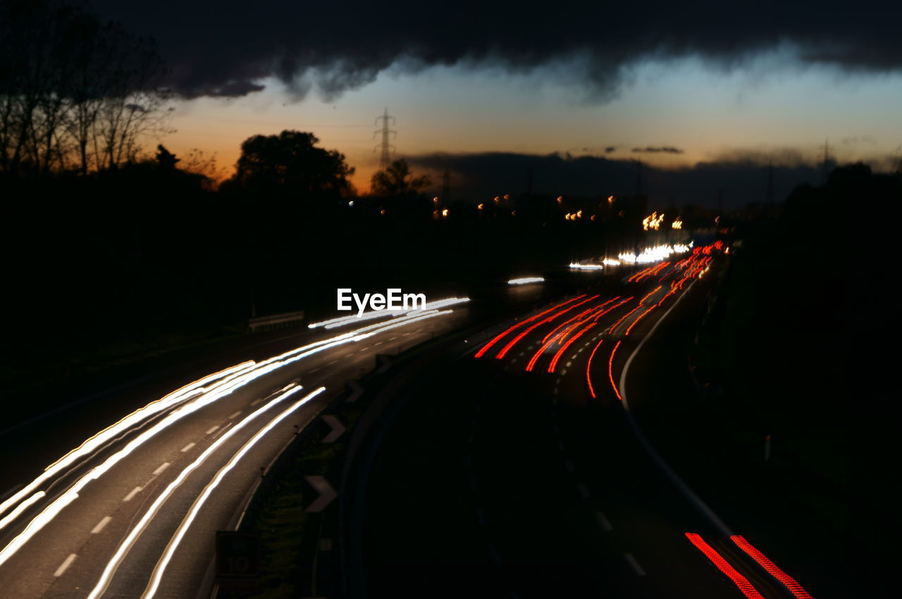 speed, light trail, road, motion, illuminated, long exposure, transportation, night, blurred motion, traffic, red, high street, no people, outdoors, sky