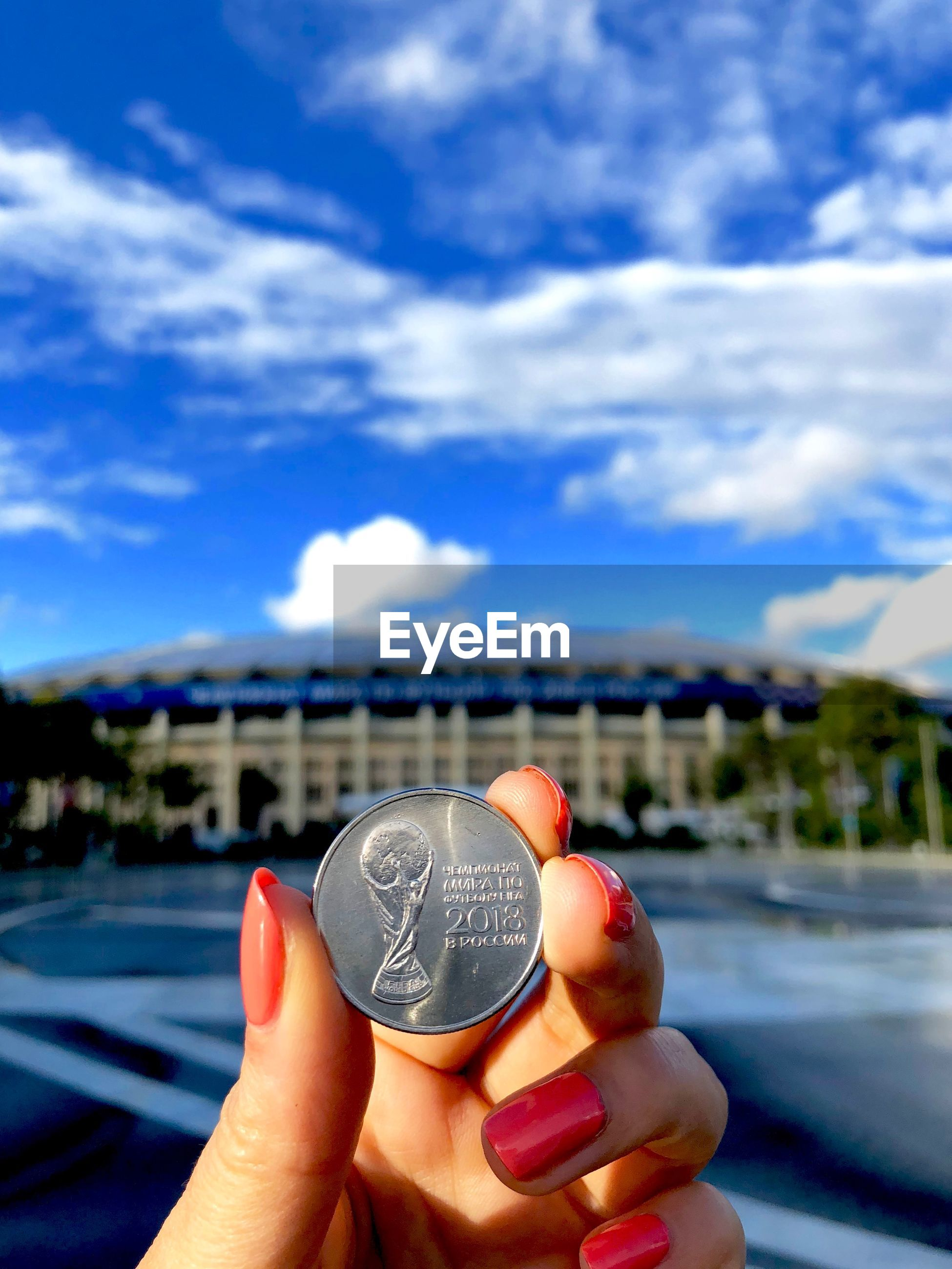 Cropped hand of woman holding coin in city against sky