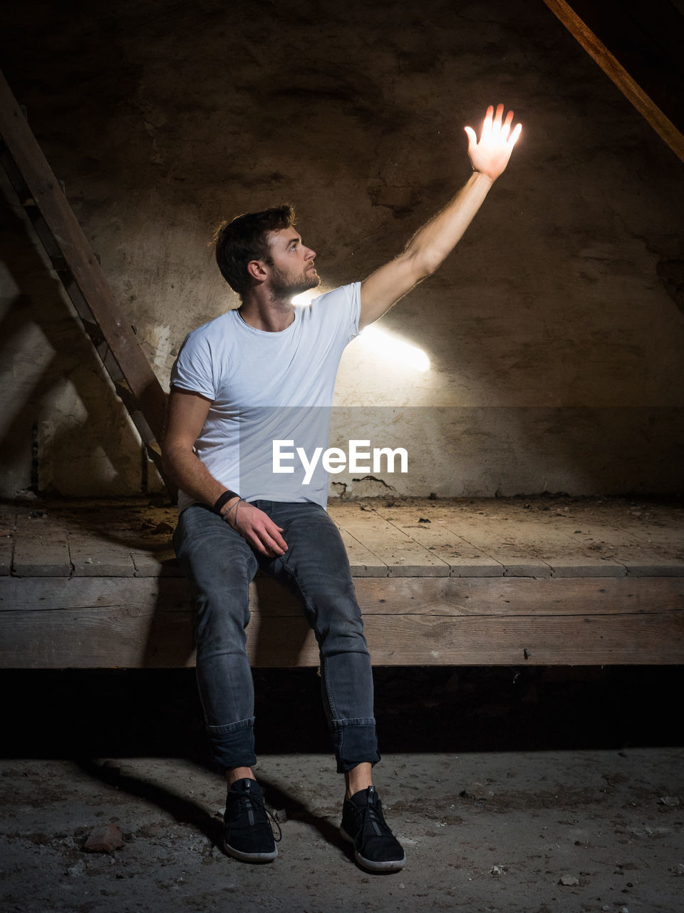 real people, casual clothing, one person, young adult, standing, lifestyles, young men, full length, front view, holding, indoors, wall - building feature, men, fire, architecture, leisure activity, burning, human arm, arms raised